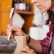 Woman Using Putty Knife On Statue — Stockfoto