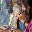 Woman Painting Jesus Christ's Statue With Paintbrush — Stock Photo