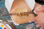 Woman's Hand Cutting Golden Paper With Knife On Board — Foto de Stock