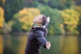 Homem com braços esticados contra lago — Foto Stock