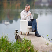 Man Using Laptop Against Lake — Stock Photo