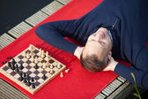 Man Lying On Pier Near Chess Game — Stock Photo