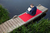 Mature Man Reading Book While Sitting On Pier — Stock Photo