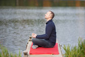 Man Meditating In Lotus Position On Pier Against Lake — Stock Photo