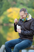 Man Dipping Tea Bag In Cup While Sitting On Fence — Stock Photo
