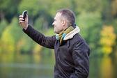 Man In Jacket Taking Self Portrait Through Mobile Phone — Foto de Stock