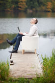 Happy Mature Man Using Laptop While Sitting At Pier — Stock Photo
