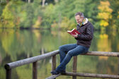 Man Reading Book While Sitting On Fence Against Lake — Stock Photo