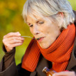 Senior Woman Drinking Syrup At Park — Stock Photo