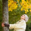 Senior Woman Holding Tree Trunk While Looking Up In Park — Stock Photo #26922147