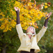 Autumn Leaves Falling On Happy Senior Woman — Stock Photo