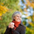 Stock Photo: Smiling Senior Woman Enjoying Coffee In Park