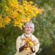 Senior Woman Holding Autumn Leaves — Stock Photo