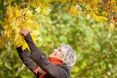 Senior Woman Holding Tree Branch — Stock Photo