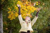 Autumn Leaves Falling On Happy Senior Woman — Stock Photo