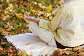 Senior Woman Meditating In Lotus Position At Park — Stock Photo