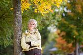 Sonriente mujer senior apoyándose en el tronco de árbol en el parque — Foto de Stock