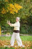 Smiling Senior Woman With Arms Raised Doing Yoga — Stock Photo
