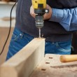 Male Carpenter Using Electric Drill At Workbench — Stock Photo