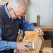 Male Carpenter Using Sandpaper For Polishing Birdhouse At Workta — Stock Photo