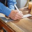 Carpenter using scale and pencil to mark on wood — Stock Photo
