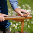 Foto Stock: Carpenter's Hands Polishing Wood In Park
