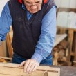 Man Wearing Red Ear Protectors While Using Table Saw — Stock Photo #26932413