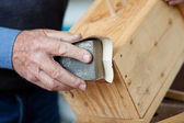 Using Sandpaper For Polishing Birdhouse At Workta — Stock Photo