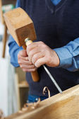 Carpenter digging hole inside a wood piece — Stock Photo