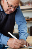 Carpenter using pencil to mark the wood — Stock Photo