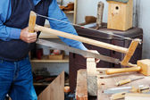 Man Cutting Wood Using Saw At Workbench — Stockfoto