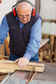 Man Wearing Red Ear Protectors While Using Table Saw — Stock Photo