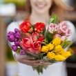 Woman showing a bunch of assorted flowers — Stock Photo #26942995