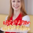 Salesgirl with Swiss cheese on a plate for tasting — Stock Photo