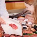 Saleslady serving sliced salami — Stock Photo #26943801