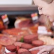 Smiling female customer selecting sausages — Stock Photo #26943861