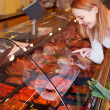 WomChoosing Meat From Glass Cabinet In Grocery Store — Stock Photo #26943999