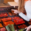 Woman purchasing meat at a delicatessen — Stock Photo