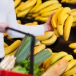 Shopper buying a bunch of bananas — Stock Photo