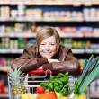 Foto Stock: Woman with a shopping cart of fresh produce