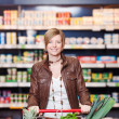 Woman With Shopping Cart In Supermarket — Stock Photo