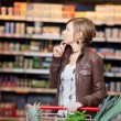 Thoughtful Woman Looking At Products In Supermarket — Stock Photo