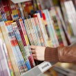 图库照片: Woman's Hands Choosing Magazines From Shelf