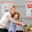 Girl And Mother Pushing Shopping Cart Together Outdoors — Stock Photo #26946185