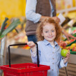 Girl Holding Shopping Basket And Apple At Grocery Store — Foto de Stock