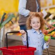 Girl Holding Shopping Basket And Apple At Grocery Store — Stock Photo #26946315