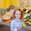 Beautiful little redhead girl with an apple — Stock Photo #26946321