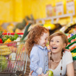Laughing mother and daughter in a supermarket — Stock Photo