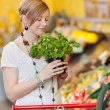 Stock Photo: Womsmelling fresh basil in supermarket