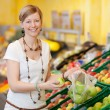 Woman Filling Plastic Bag With Apples In Grocery Store — Stock Photo #26947031